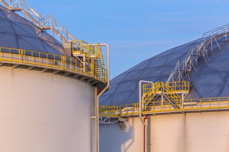 bp: Modern oil storage tanks with Detail of steps and stairs on an industrial harbor area in warm sunset light in the Netherlands