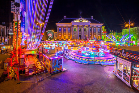 GRONINGEN, THE NETHERLANDS-MAY 5,2015: Annual Funfair during may holidays on the Grote Markt cenral city square. Long exposure image at night with blurred movement. Editorial
