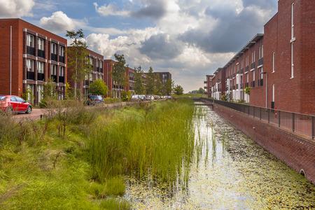 clase media: Calle moderna con las casas de la familia de clase media ecológicos con el banco ecológico del río en una zona suburbana de la ciudad de Wageningen, Países Bajos Foto de archivo