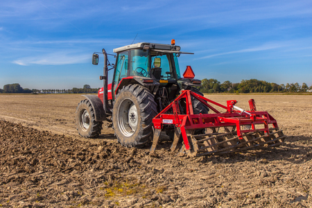 plough machine: Field being ploughed by tractor with Plough under Blue Sky. Farming scene in the Netherlands,