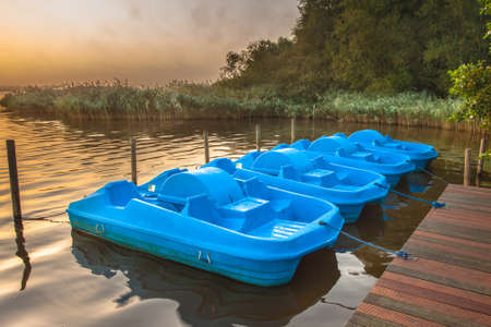 peddle: Row of Blue Pedal Rental Boats on a Foggy Morning at Zuidlaardermeer, Netherlands Stock Photo