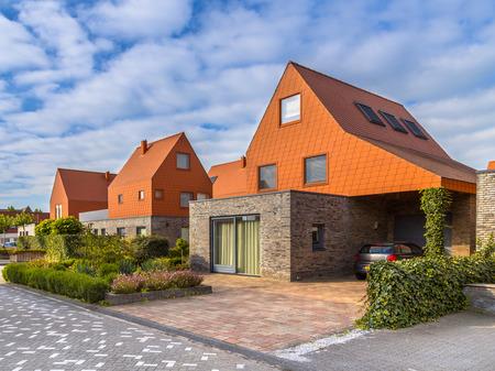 hilera: casas de la arquitectura moderna con tejas de color rojo notables en un barrio suburbano contempor�neo en los Pa�ses Bajos