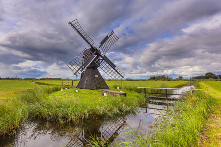 drain water: Black Wooden Windmill. Historic water management pump device to drain water from a Polder, Netherlands Stock Photo