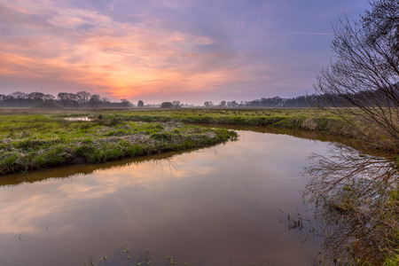 silt: Sunset over a lowland meander in the Regge river, Twente Netherlands. A meander forms when moving water in a stream erodes the outer banks and widens its valley, and the inner part of the river has less energy and deposits silt. Stock Photo