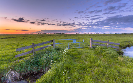 dikes: Purple sunset over fence in flat countryside near Groningen Stock Photo