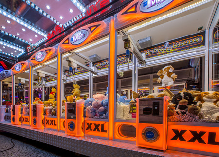GRONINGEN, THE NETHERLANDS-MAY 5, 2015: Arcade crane vending machine with colourful orange lights on the annual funfair on central square.