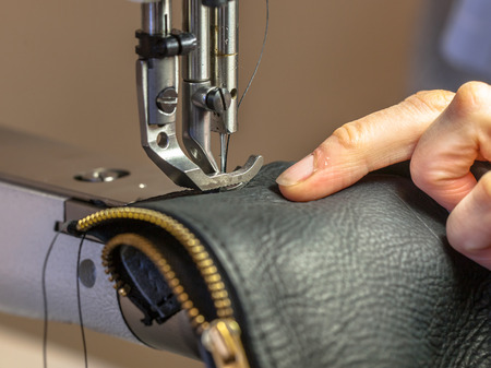 manufacture: Industrial Sewing machine in action with hands working on a leather shoulder bag Stock Photo