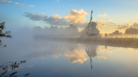 fog white: Reflection of White wooden windmill in river with morning fog during sunrise, Drenthe, Netherlands Stock Photo