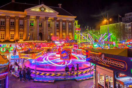 square image: GRONINGEN, THE NETHERLANDS-MAY 5,2015: Annual Funfair during may holidays at the Grote Markt city hall on the cenral city square. Long exposure image at night with blurred movement.