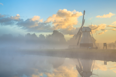 fog white: White wooden windmill at river in morning fog during sunrise, Drenthe, Netherlands