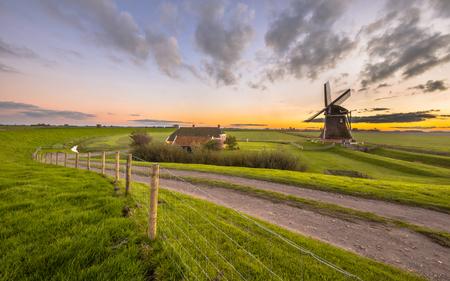 Ultra groothoek toneel van Nederlandse Houten windmolen in flat met gras begroeid landschap onder de prachtige zonsondergang gezien vanaf de zee dijk bij Waddenzee, Nederland