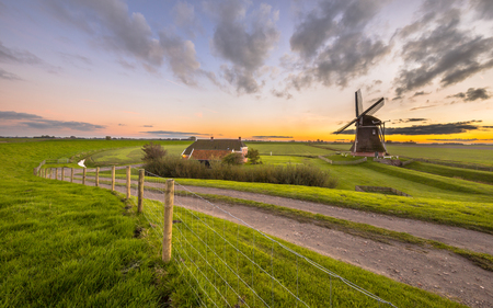 Ultra wide angle scene of Dutch Wooden windmill in flat grassy landscape under beautiful sunset seen from the sea dike at Waddensea, Netherlands