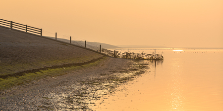 coastal: Delta works Sea dike of the Waddensea in orange haze around sunset in Friesland, the Netherlands