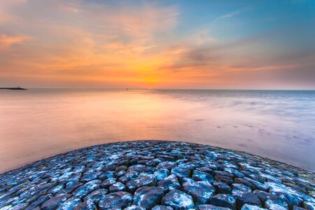 head protection: Sunset over Waddensea from the head of a Stone Waterflood Protection Pier