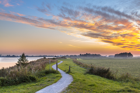 Holland Polder landscape with winding cycling track along river under beautiful sunset