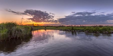 dikes: Sunset over aquatic farmland in natura 2000 area Zuidlaardermeergebied near Groningen Stock Photo