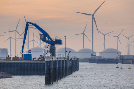 construction equipment: Hydraulic blue Harbor Crane in the port of Eemshaven under setting sun