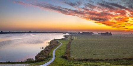 polder: Aerial panorama of Netherlands Polder landscape with winding cycling track along river under beautiful sunset