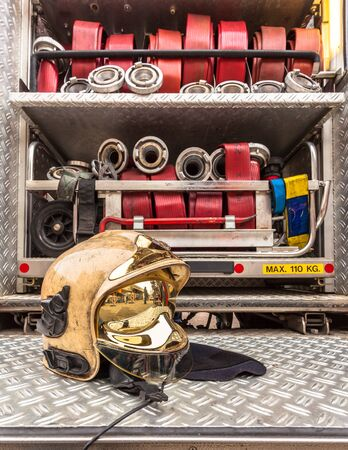 fire brigade: Modern Golden Fire Brigade Helmet and Other Inventory of a Fire Engine Stock Photo