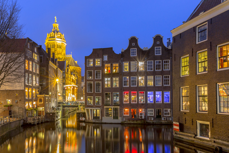 canal houses: Nightscape of colorful traditional waterfront canal houses at night seen from the armbrug on the Oudezijds Voorburgwal in the UNESCO World Heritage site of Amsterdam Editorial