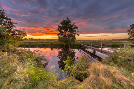 stroll: Landscape with Wooden pedestrian bridge over river in dutch countryside near Groningen under purple sunset during a sunday afternoon stroll in august