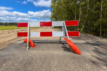 road closed: Red and white no entry roadblock on a small asphalt country road