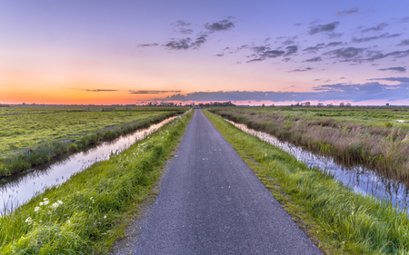 Road with ditches in flat and open polder countryside in Holland