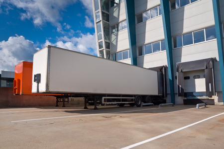 loading bay: Red and White Trailer in Front of Docking Bay of a distribution centre ready for Transport