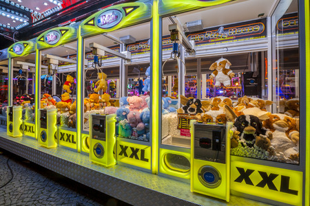 vending machine: GRONINGEN, THE NETHERLANDS-MAY 5, 2015: Arcade crane vending machine with colourful yellow lights on the annual funfair on central square.