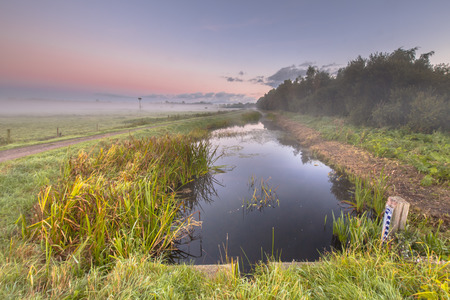 dikes: Early Morning scene of a  canal with water level measuring rod of dutch waterschap or body of survey of dikes. Stock Photo