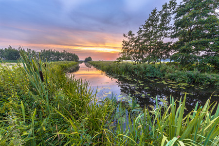 upstream: River Koningsdiep flowing through frisian lowland valley countryside at dusk Stock Photo