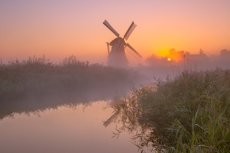 Characteristic historic windmill along a river in a polder wetland on a foggy september morning in the Netherlands