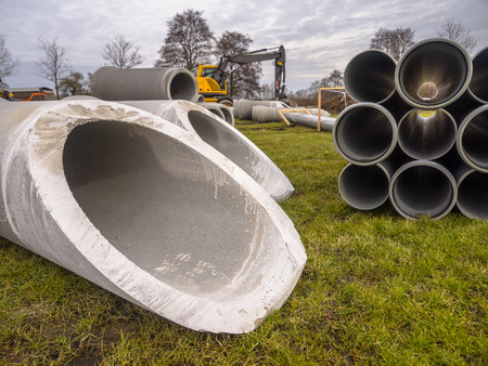 construction material: Concrete pipes and plastic draines with other building material on a construction site
