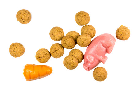strooigoed: Handful of Pepernoten cookies with marzipan pig and carrot Sinterklaas decoration on white background for dutch sinterklaasfeest holiday event on december 5th