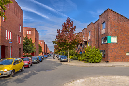 Street with modern suburban family row houses in a suburban neighborhood with trees and gardens Editorial