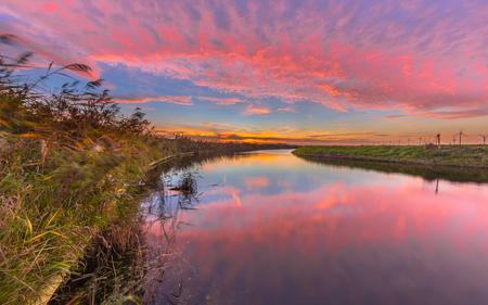 Colorful pink and orange sunset over meandering Groote Tjariet river in Netherlands landscape