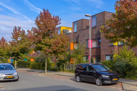 Colorful modern suburban teraced family houses in a lively proper neighborhood with trees and gardens Stock Photo