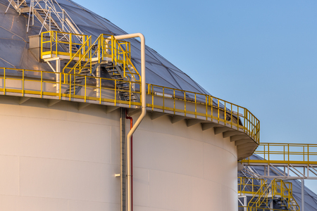 Modern big oil storage tanks with Detail of steps and stairs on an industrial harbor area in warm sunset light in the Netherlands