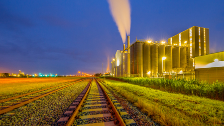 Colorful Panorama of Railroad in a heavy Industrial Chemical area with mystical dreamy colors and lights in twilight Stock Photo
