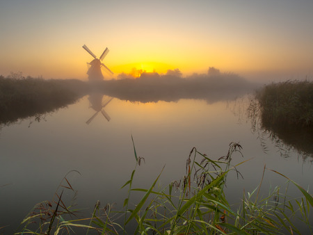 Traditional dutch Windmill on a lake duringn a hazy morning sunrise in september