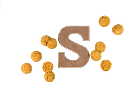 zwarte: Dose of Pepernoten cookies or ginger nuts with chocolate letter as Sinterklaas decoration on white background for dutch sinterklaasfeest holiday event on december 5th