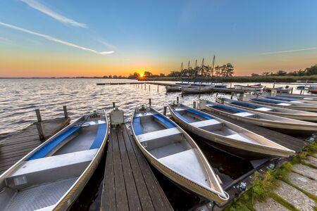Rij van huurboten in een Nederlandse haven, terwijl de zon opkomt boven de horizon