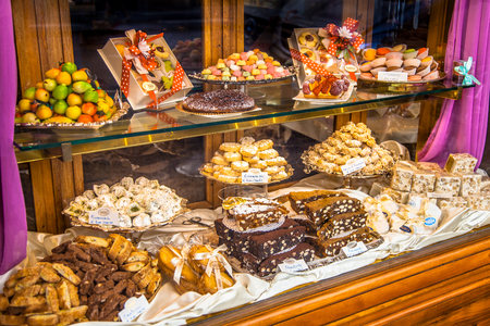 Traditional Italian Pastry shop glass display with selection of nougat, cookies, cake and sweets 免版税图像