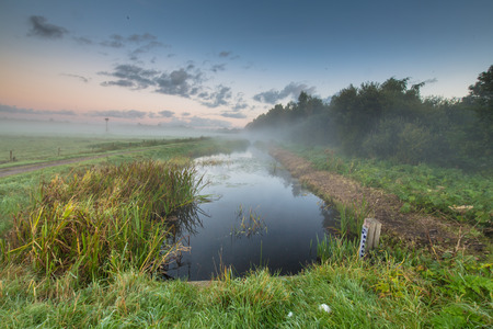dikes: Sunrise over river with water level measuring rod of dutch waterschap or body of survey of dikes. Stock Photo