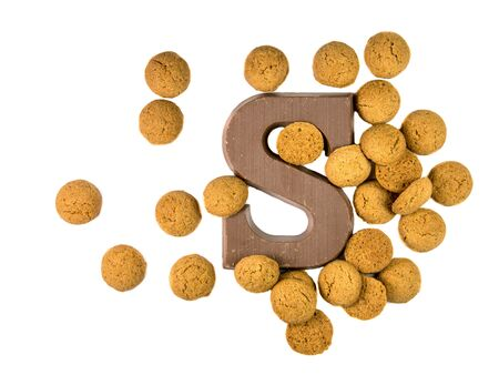 strew: Bunch of Pepernoten cookies or ginger nuts with chocolate letter as Sinterklaas decoration on white background for dutch sinterklaasfeest holiday event on december 5th