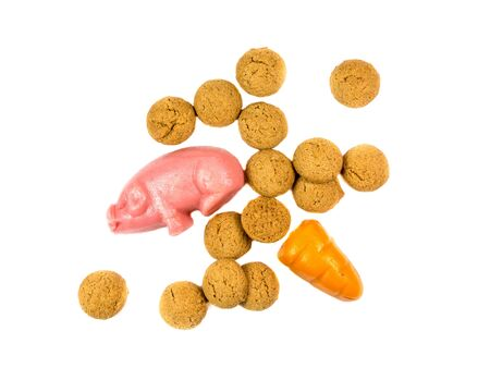 Group of Pepernoten cookies with marzipan pig and carrot Sinterklaas decoration on white background for dutch sinterklaasfeest holiday event on december 5th