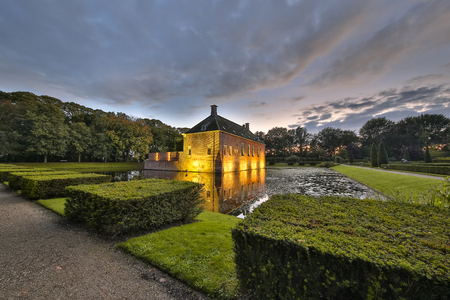 14th century: Verhildersum castle or borg  with symetrical buxus. This fortified house was built in the 14th century to defend the area against intruders around Leen, Netherlands