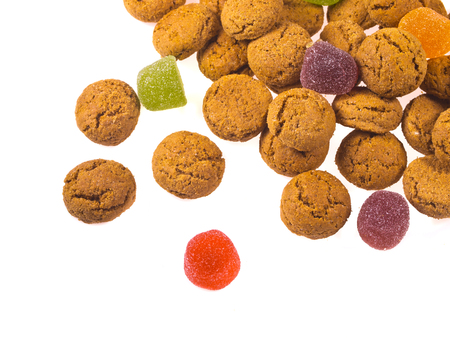 strew: Toss of Pepernoten cookies and sweets seen from above as Sinterklaas decoration on white background for dutch sinterklaasfeest holiday event on december 5th Stock Photo