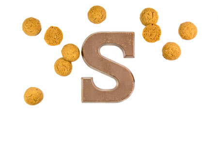zwarte: Handful of Pepernoten cookies or ginger nuts with chocolate letter as Sinterklaas decoration on white background for dutch sinterklaasfeest holiday event on december 5th Stock Photo