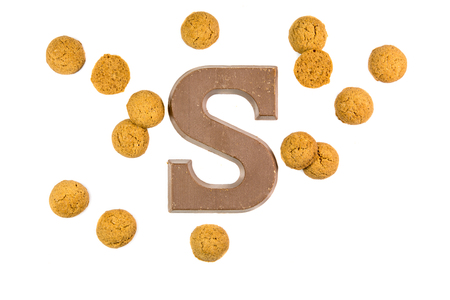 Handful of Pepernoten cookies or ginger nuts with chocolate letter as Sinterklaas decoration on white background for dutch sinterklaasfeest holiday event on december 5th Stock Photo